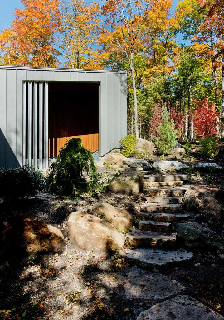 From the entrance, more of the broken stone pathway leads around the home toward the patio and lake.