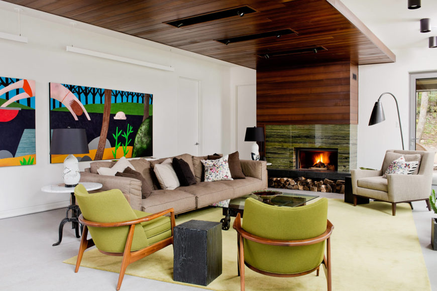 The marble wrapped fireplace extends into a rich wood paneled ceiling that arches over the living room. Contemporary seating in beige meets a pair of lime green chairs over a light hued area rug.
