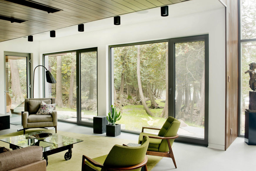 Turning toward the rear of the home, we see how the full height glazing and extensive glass doors blend the interior with the surrounding environment. Natural light spills through the entire space.
