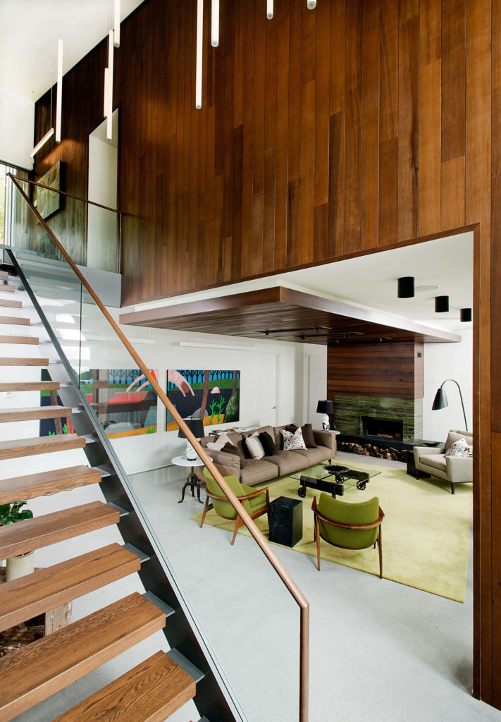 The entry leads into an upper level, spilling downward over the floating hardwood stairs into the living room visible at center. Bright colors interact with the neutral and natural tones throughout.