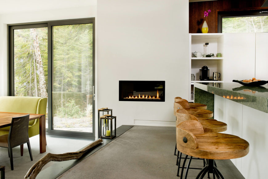 Beneath the green granite countertops we see a set of rustic wood bar stools, with a discreet gas fireplace built into the wall at center. Sliding glass doors allow outdoor access via the dining room.