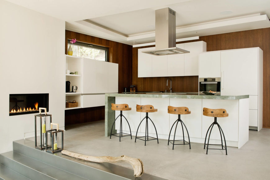 The entire kitchen space, wrapped in hardwood paneling, spills out into the open-concept area over a set of metallic steps in the foreground.