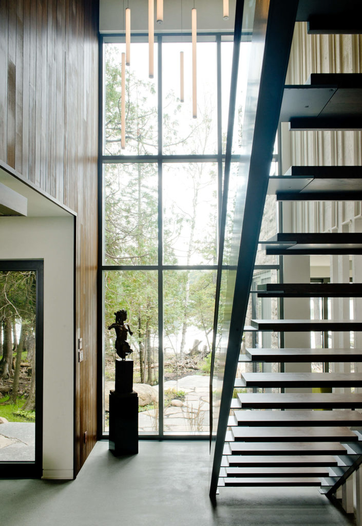 Seen from below, the open design staircase allows light and airflow, keeping the central space airy and bright. The two story window panels here grant expansive views.
