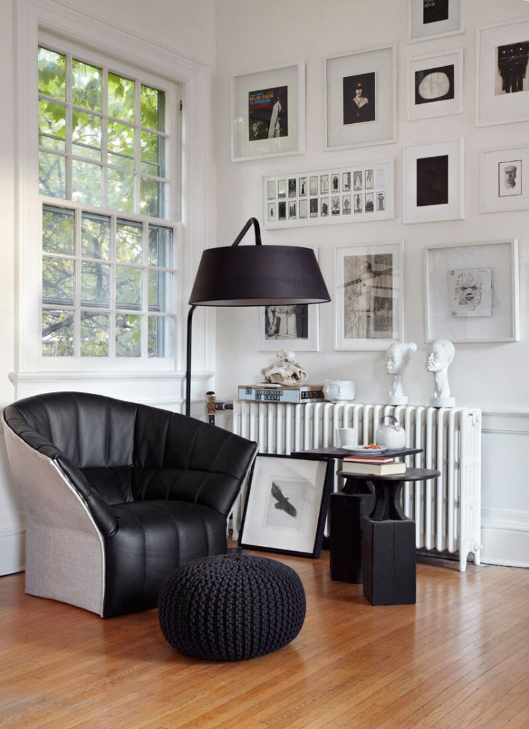 Next to an old fashioned radiator heater, this contemporary black leather armchair stands with a pair of matching tables and a plush, oval beanbag ottoman. Paintings and photographs add contrast and detail to the white walls.