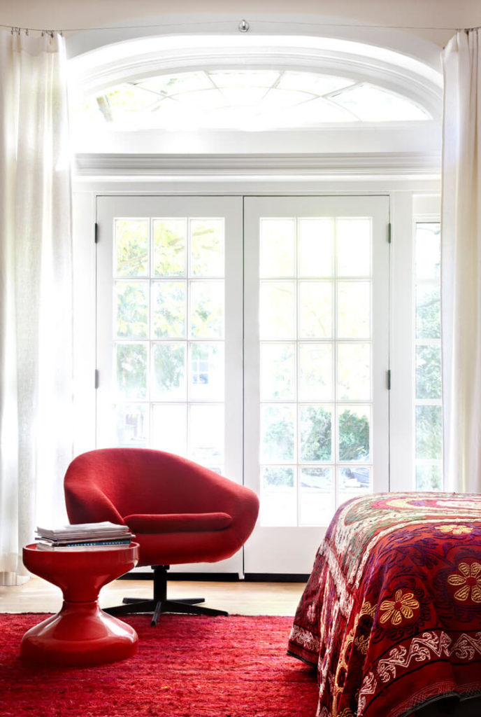 The bedroom continues the bright red tones of the prior space, with the unique modern swivel chair and hourglass-shaped table standing before French patio doors.
