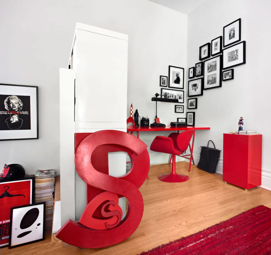 This home office space features a distinctly red theme, with rug, desk, chair, and other artful details contrasting with the predominant white and black tones. More black and white photography adorns the walls.