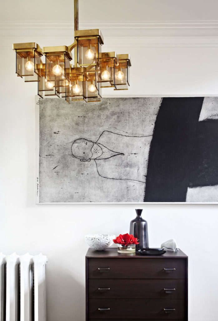 The ornate, cubic chandelier in this space adds a splash of gold to the monochrome area, with a large painting hanging over dark stained wood dresser.