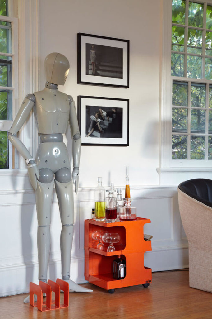 In this part of the vast living room, we see another burst of orange, with a portable drink cart standing next to a full sized, posable human figure. Greyscale photography on the wall hangs in counterpoint, matching the understated structure of the home.