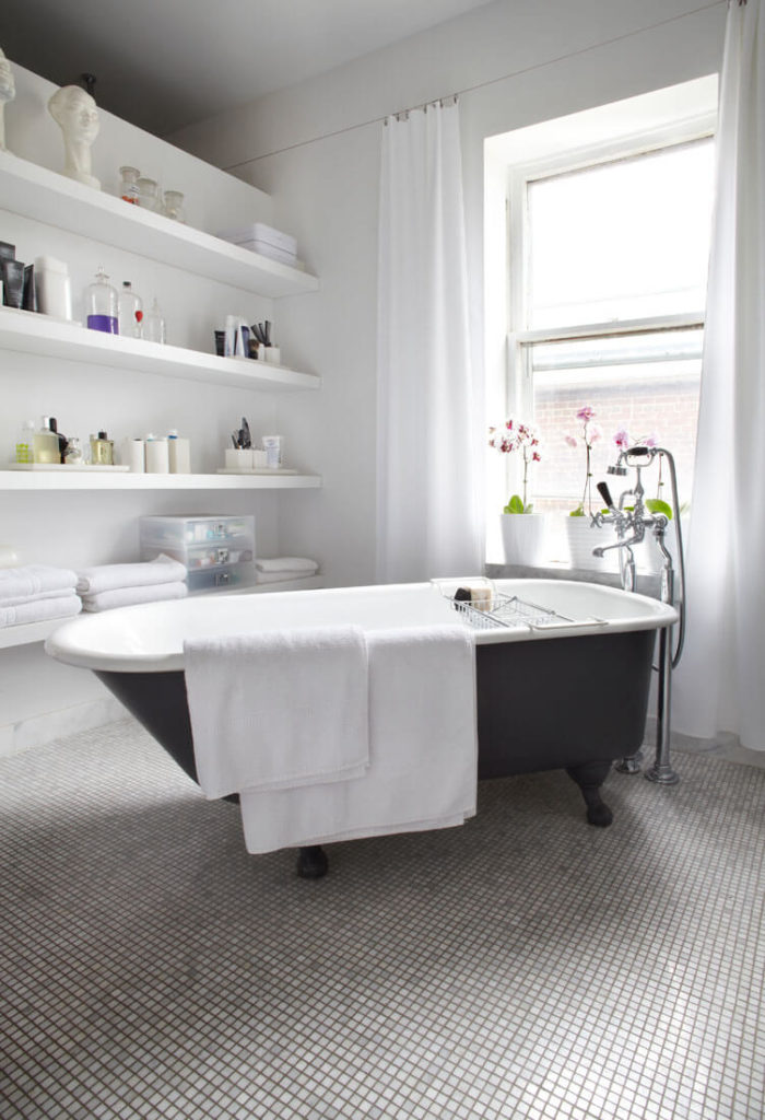 The primary bath houses this traditional claw-foot tub over micro-tile flooring. White shelving and drapes brighten the space.