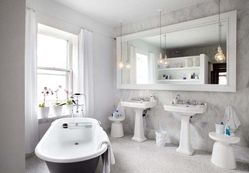 The bathroom houses an oversized mirror against a full height marble wall, with a pair of pedestal sinks in white below.