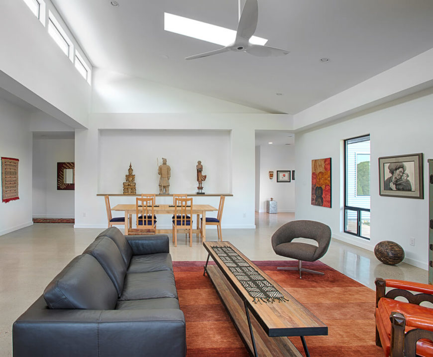 The unique seating options center on a rust-spectrum colored rug over an expanse of granite flooring. White walls help accentuate the various artistic and furniture elements throughout.