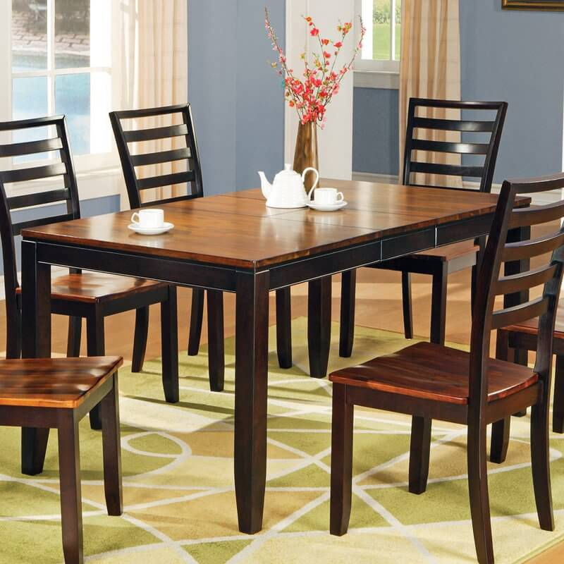 This ultra-sleek dining room table features intricately carved construction, with bright natural wood surface over a richly dark stained structure. Butterfly leaf design ensures easy storage and high utility.