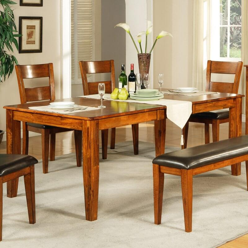This wood dining room table features a brightly welcoming natural wood tone, rich with textural nuance. The simple four leg design appears timeless and sturdy.