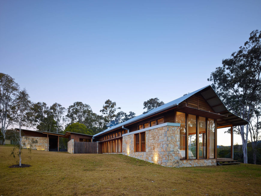 The sprawling structure stands surrounded by eucalypts and undulating landscape. The rich natural wood and stone textures make the home of-a-piece with its environment.