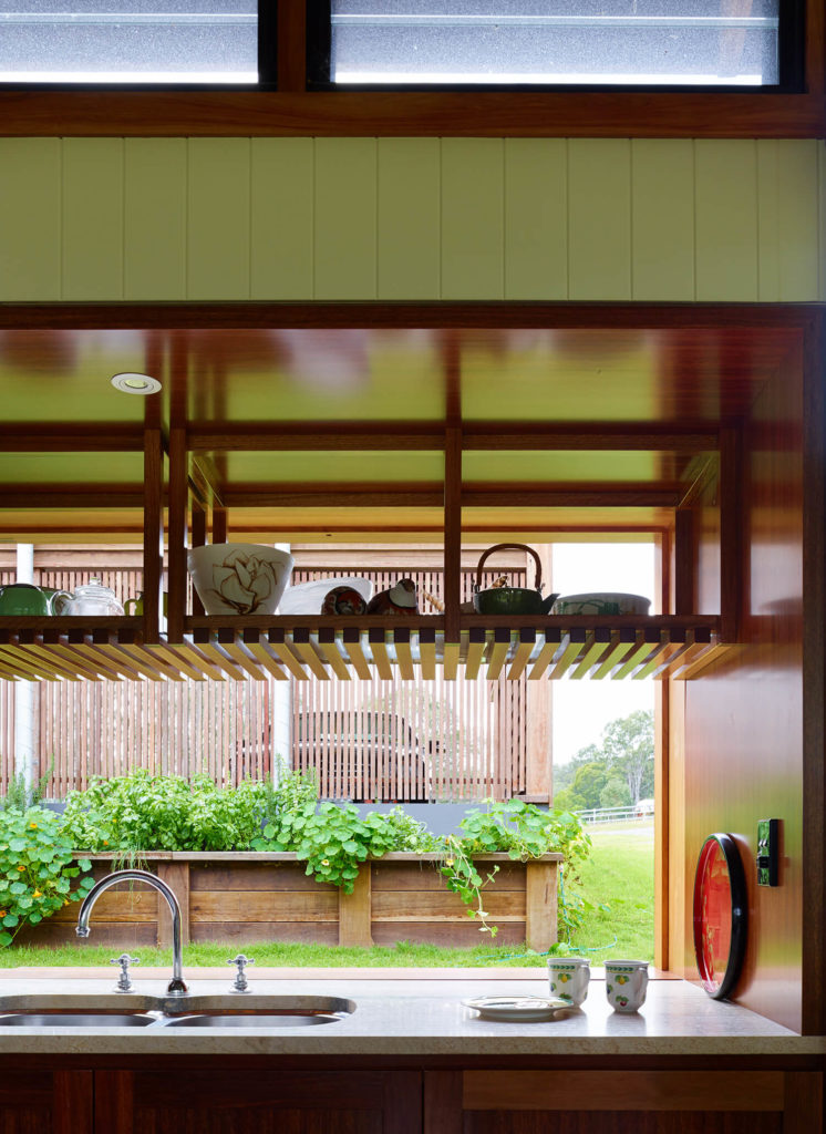 Looking over the granite countertop of the kitchen, we see a container garden and lawn through large scale sliding glass window. Built-in shelving and natural wood cabinetry are some of the highlights here.