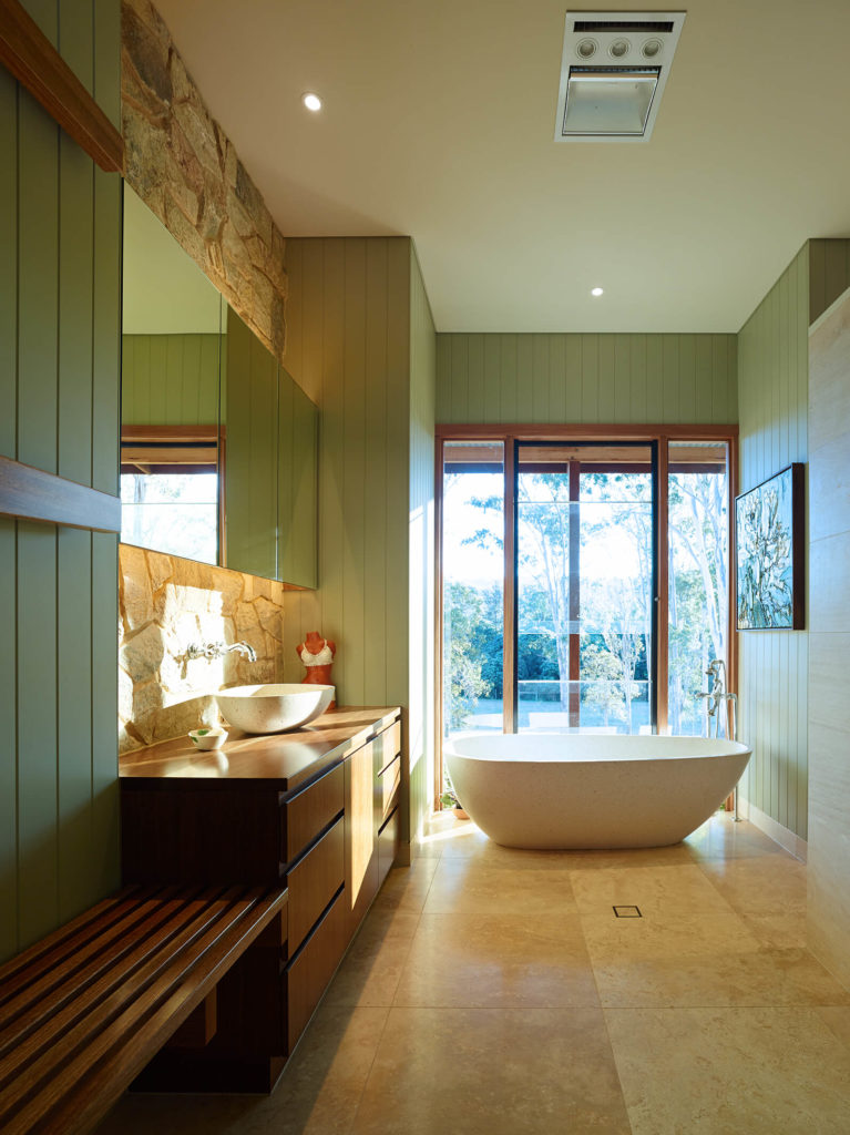 The bathroom features a large pedestal tub beneath full heigh windows, standing on large format tile flooring. Rich wood vanity with vessel sink features a frameless mirror mounted on stone backsplash.