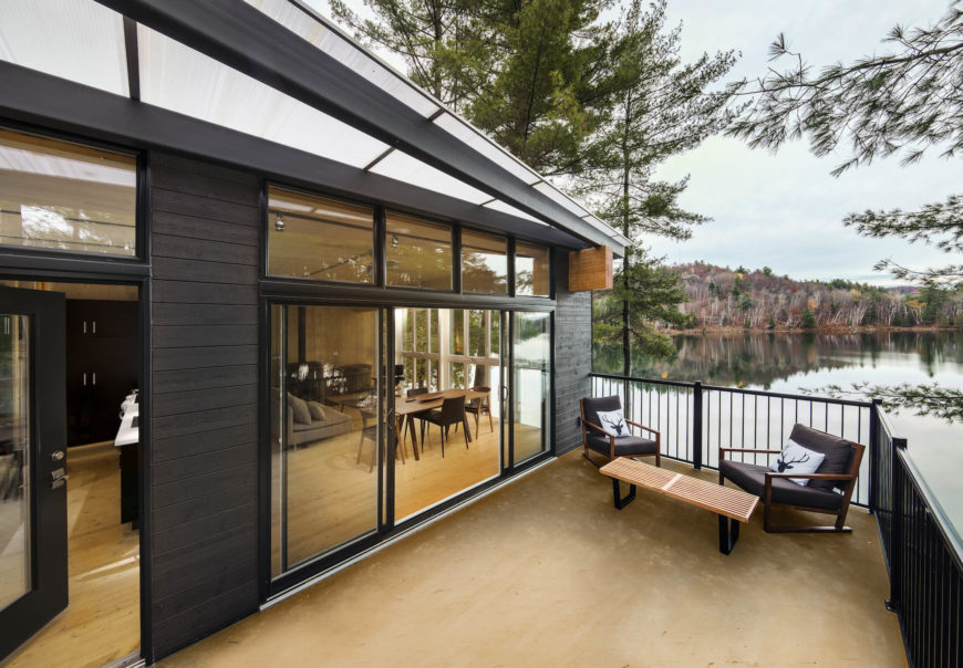 On the patio, we can see through the massive sliding glass doors into the natural wood bedecked interior. A simple slatted bench and pair of wood frame armchairs sit on the lake side, wrapped in black fencing.