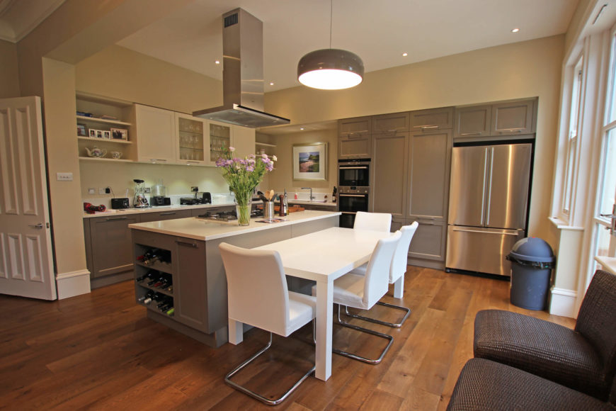 This rich, expansive kitchen centers on the large, incredibly useful island with built-in wine rack and cooktop, next to a pristine white dining table.