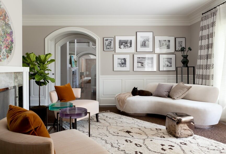 A beautiful contemporary living room featuring two small end tables, each with a different colored glass top. The bold color in the tables, along with the rust colored throw pillows, add life and color to this otherwise neutral living room. In the corner is a white kidney shaped sofa.