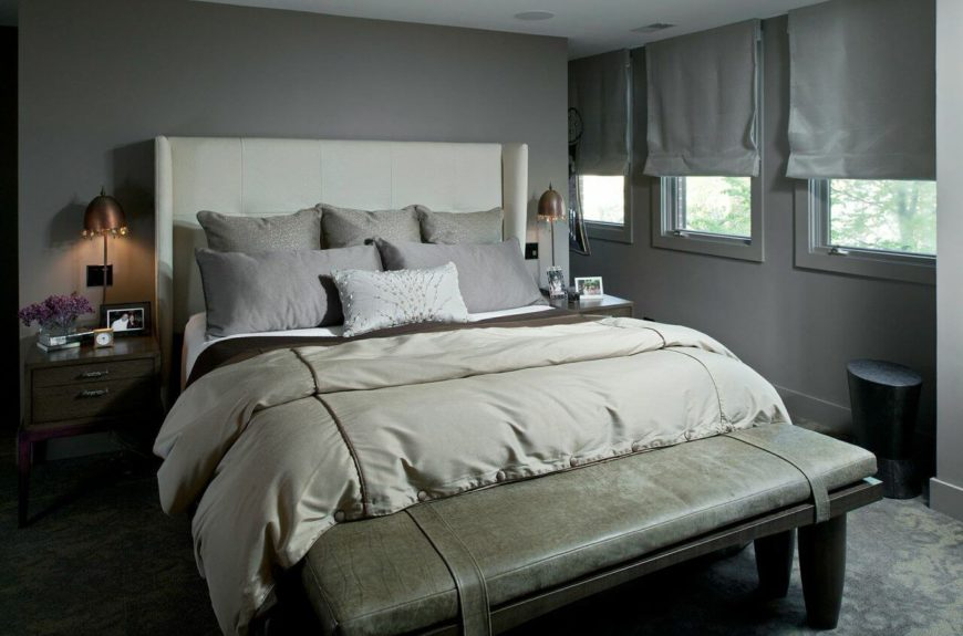 The primary bedroom is in a very contemporary gray with an upholstered wingback head board. The bench at the foot of the bed is in a subtle, light green alligator skin pattern.