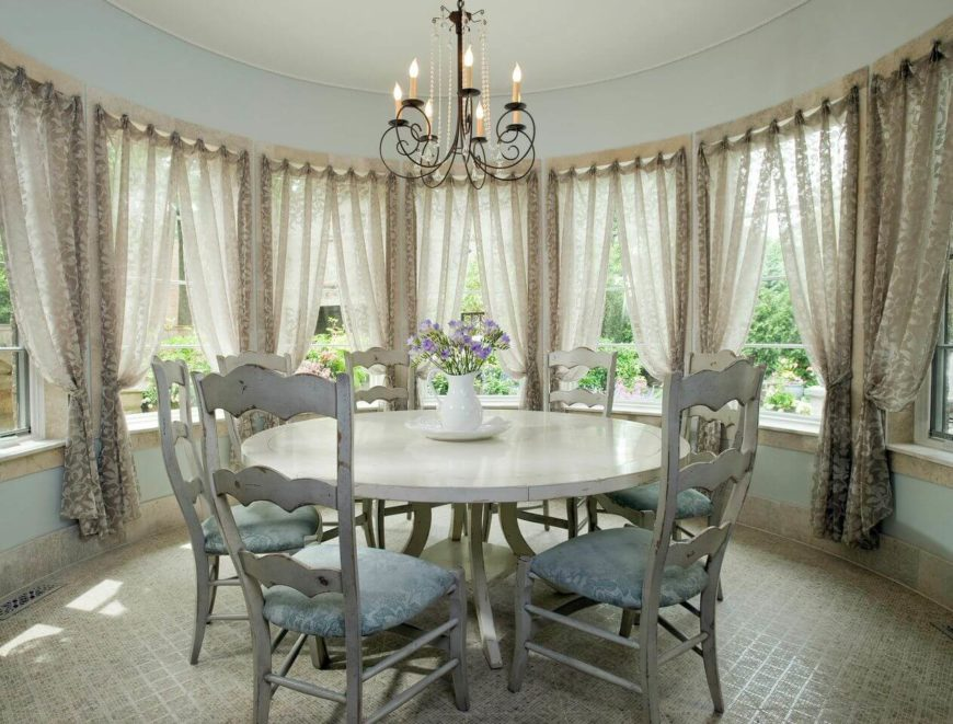The nook extending from the kitchen is circular and in a light, powdery blue. The tile floor catches the light. A distress white circular dining set is topped by a crystal and wrought iron chandelier.