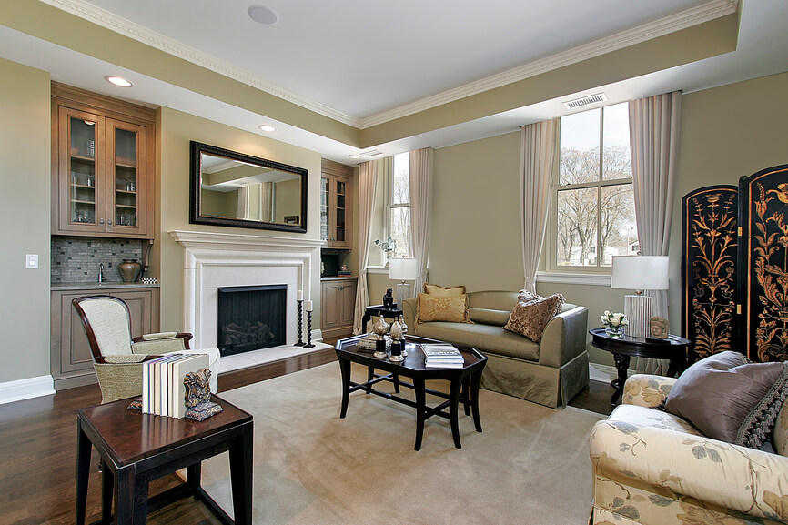 A spacious living room with two large end tables on opposite sides of the room and a third smaller one tucked into the corner near the built-ins. The round end table is next to the screen and the larger square table is between the two upholstered chairs.
