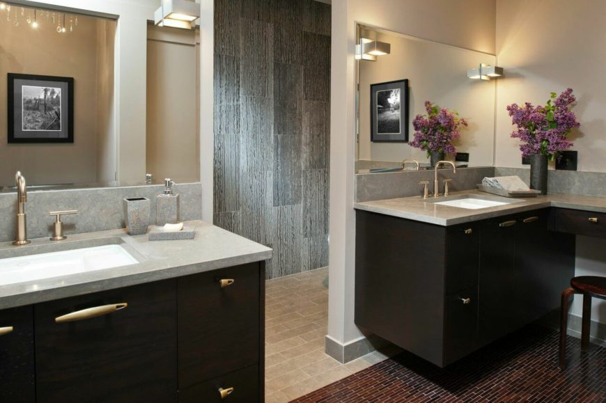 A jack-and-jill bathroom with dark wood vanities and a glass-tile floor in brick red. The mirrors continue around the corner of each wall. The light gray countertops are warmed by the subtle gold fixtures.