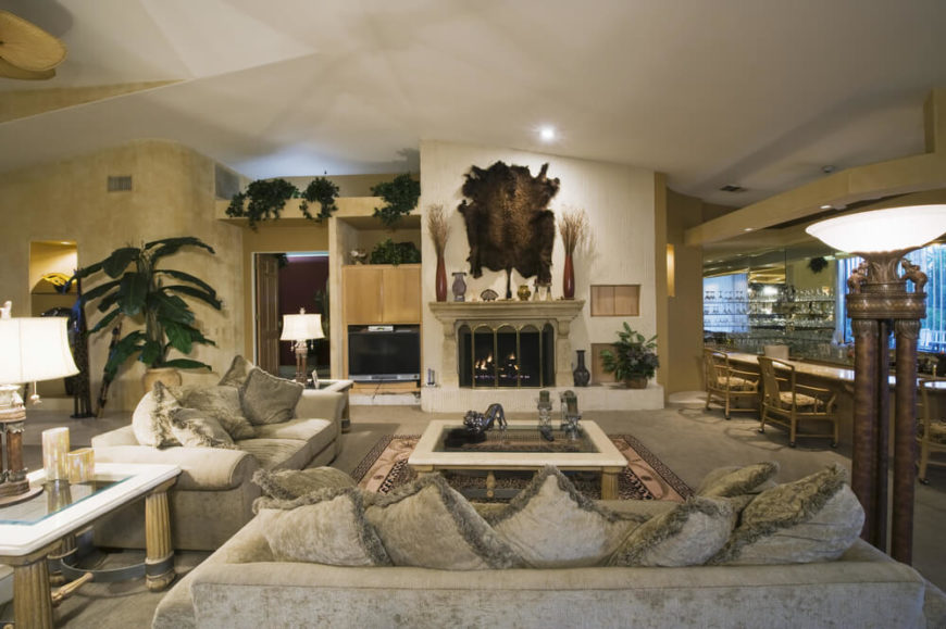 A swanky living room with velvet sofas and a stately fireplace. An enormous end table that matches the coffee table has fluted legs and a glass top. To the right is a large wet bar with an eat-in countertop. The tile accent wall behind the fireplace is a great contrast to the textured walls on either side.