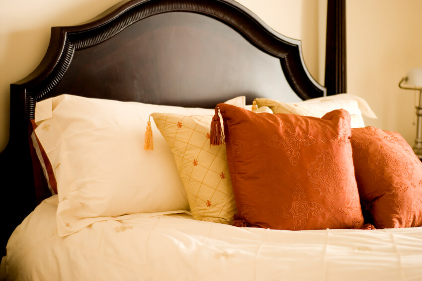 Rust orange and yellow pillows with corner tassels rest against the neutrality of a delicately embroidered cream bed pillow. A dark headboard offers optimal contrast for additional beauty and interest.