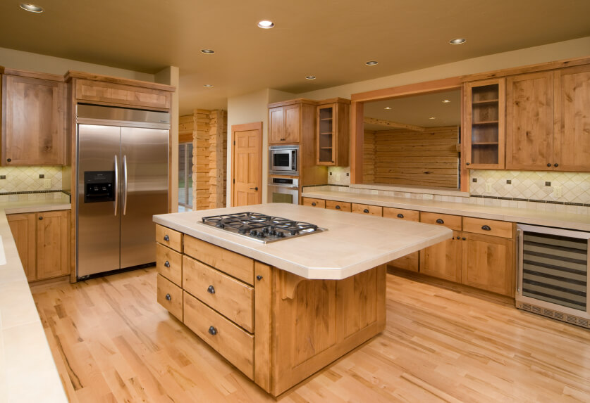 This neutral kitchen works well to accent the beautiful quality of the natural wood cabinetry and the varying tones of the flooring. Beige countertops and backsplashes connect expanses of natural wood.