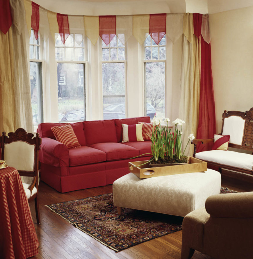 The festive cream and light red valance adds a whimsical air to this otherwise simple, contemporary living room.