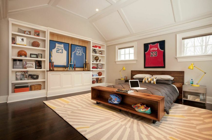 Another enormous bedroom filled with basketball memorabilia. The footboard of the bed has open shelving. The adjustable bedside lamps pull out some of the yellow in the area rug. The barrel vaulted ceiling is a beautiful architectural detail.