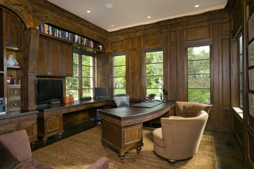 The elegant home office has lovely crown molding, paneling, and built in desks. A matching curved desk extends from the back wall into the center of the room.