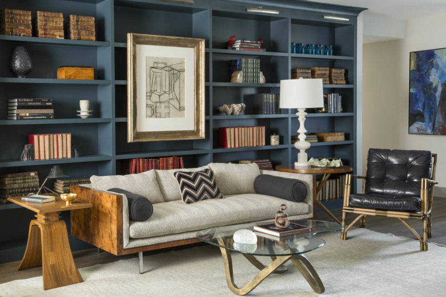 A bold and masculine living room with large built-in blue bookcases behind the wood and linen sofa. The two mismatched end tables in this room are both all wood, and are topped with a lamp and small accents.