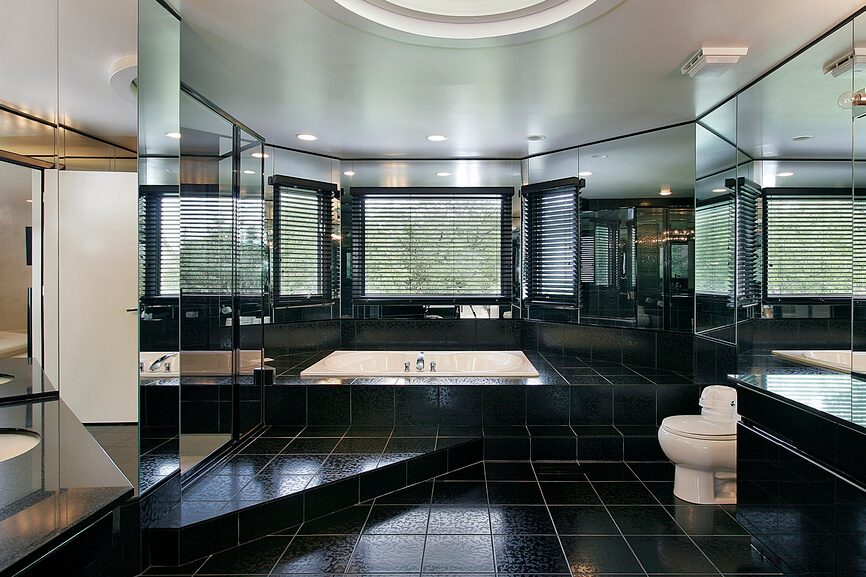 This ultra-luxurious bathroom stands with wraparound mirrors on every vertical surface, over a sea of black tile flooring. The varied-height floor rises to enclose a soaking tub beneath an array of windows.