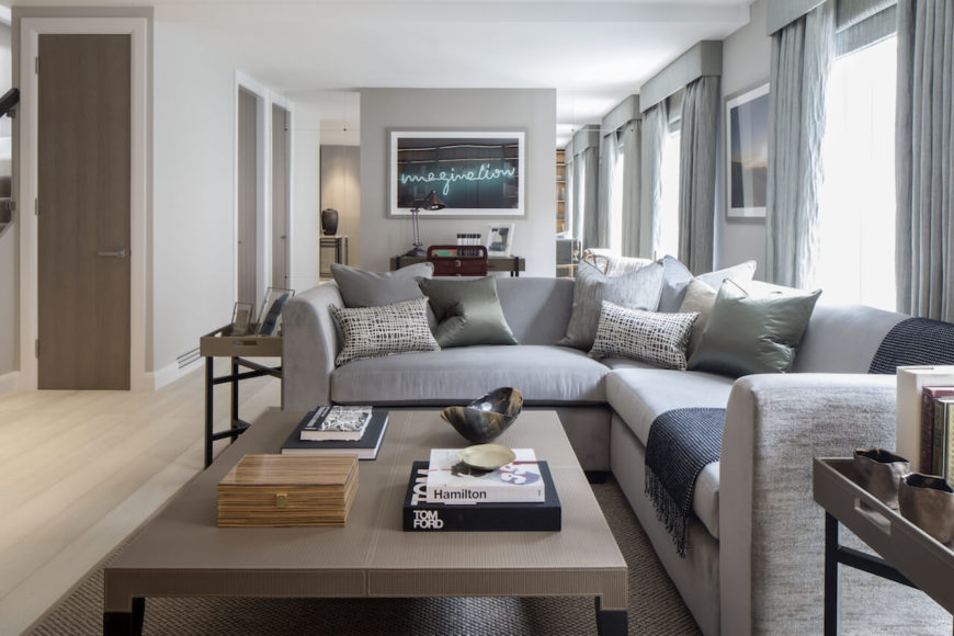 A casual living room in grays with a small home office area to the rear of the room. The side tables in this space are utterly simple, with thin legs and a tray top. The beige tops and dark legs perfectly match the large coffee table in front of the sectional.