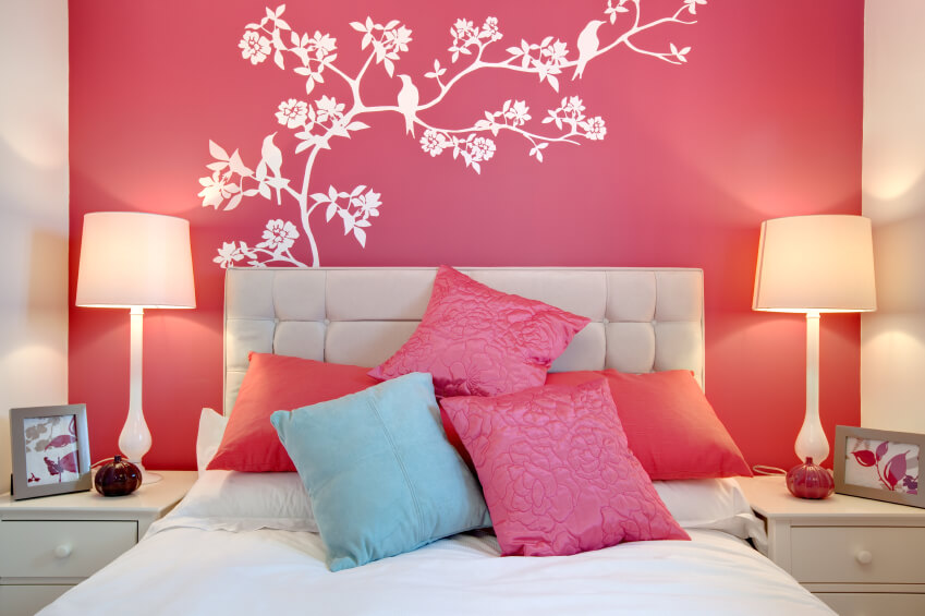 Stunning wall art steals the show in this bold, vibrant space. The art stands out in stark white contrast to the vibrant pink of the wall. A beige headboard complements the matching end tables and lamps, while additional pink, fuchsia, and blue pillows are tossed playfully upon the bed.