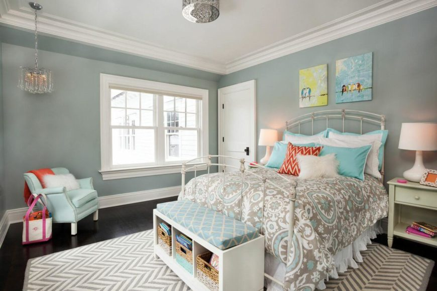 A stylish feminine bedroom with a white wrought iron bed frame and a color palette of gray, light blue, and orange. On the wall behind the bed are two small paintings.