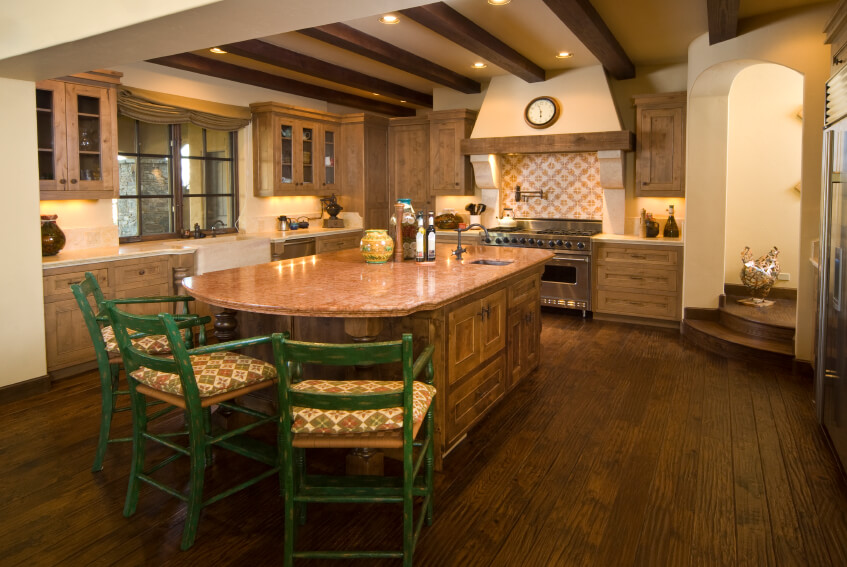 This large kitchen has a gorgeous vent hood and a island with a table extension. The wooden floors are a rich dark color, with natural texture and hues.