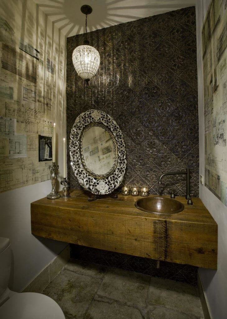 The inside of the powder room continues the same style as the foyer with aged natural stone floors, a reclaimed wooden vanity and a brushed bronze sink. The ornate tile above the vanity is uninterrupted by a mirror. The mirror is instead on a small holder beside the sink.
