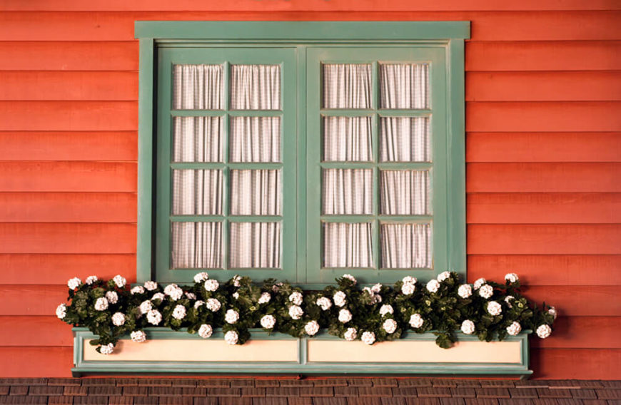 A cream and pale green window box that contrasts beautifully with the brick-red siding of the home. The small, white pom-pom shaped flowers and dark green leaves draw the eye.