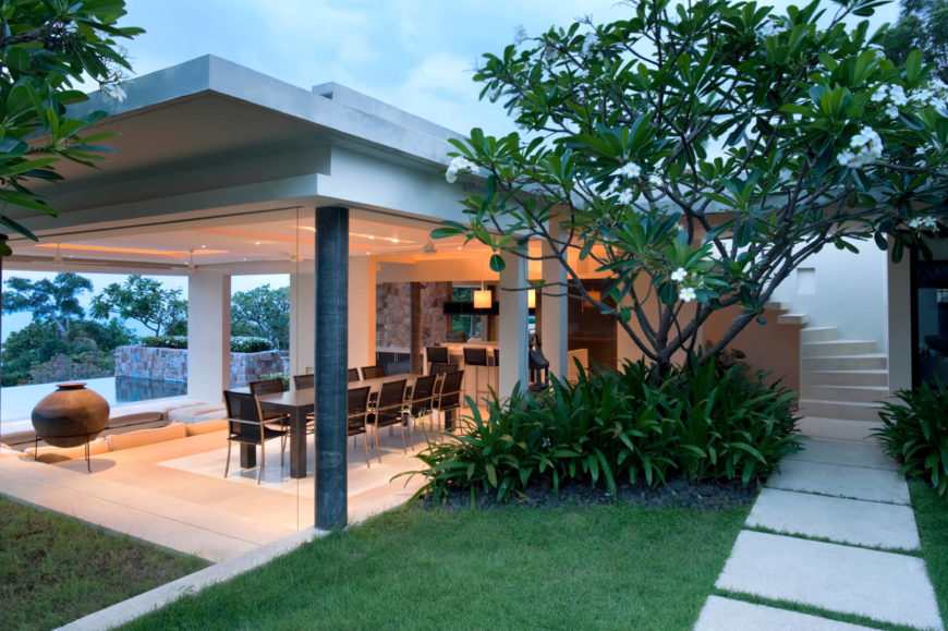 The sprawling home is separated into two sections, with outdoor pathways connecting. Beautiful landscaping punctuates each pathway. From this view, we can see a section of the infinity pool through a glass-enclosed dining room and another kitchen and bar area. A set of stairs spiral up to the second floor.