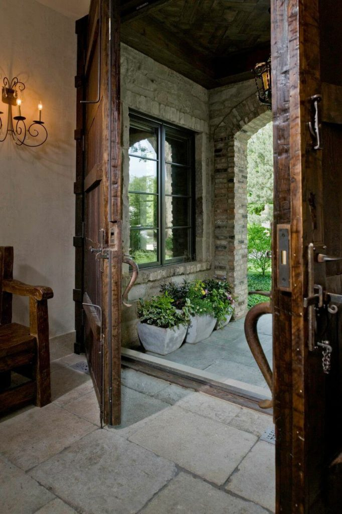 The enormous wooden double doors that mark the entrance to the home lead into the natural stone floor foyer. To the left of the doors is an antique wooden bench.