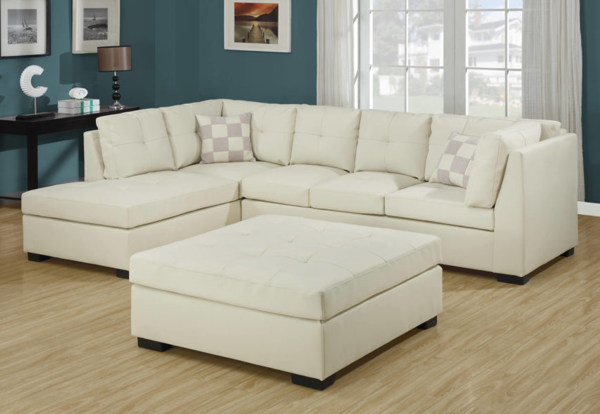 A large tufted ottoman the same height as the sofa. The square design makes it easy to push against the couch to create a cozy nest, or against the short chaise to create a longer chaise.