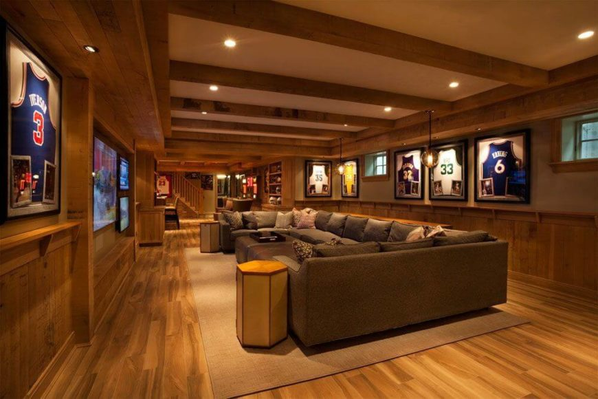 On the other side of the room is the cavernous family room with a huge U-shaped sectional sofa with several ottomans. The walls are decorated with framed jerseys. The left wall has one large television and two smaller ones beside it for an optimal game watching experience.