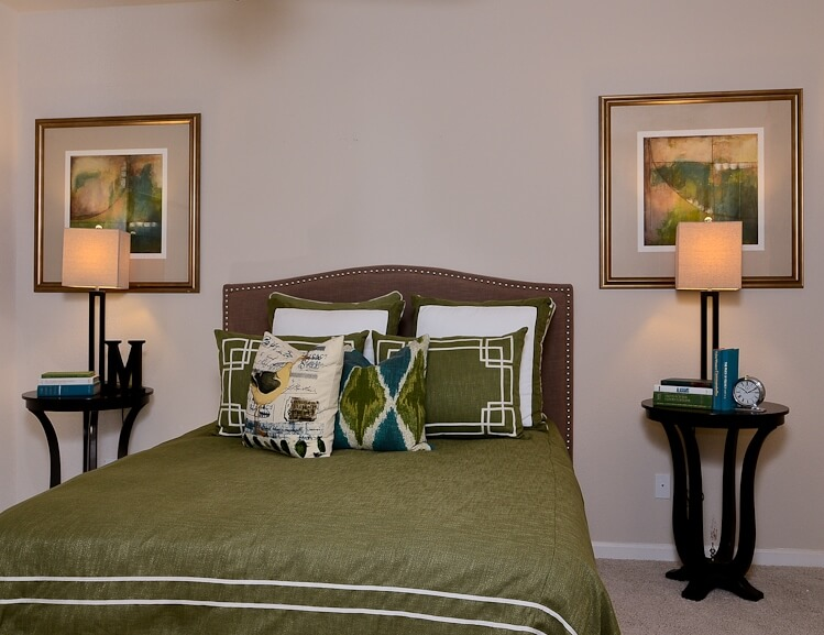 This bespoke bedroom features a rich leather headboard behind green bedding, flanked by a pair of black side tables with complementary lamps. Matching paintings hang above.
