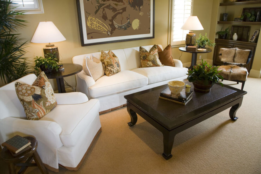 A formal living room with three end tables positioned so that every seat in the room has access to a table. Next to the white armchair is a small wooden stool repurposed as an end table. Between the white chair and loveseat is a larger end table in dark wood. A matching table sits between the sofa and the hide chair to the right.