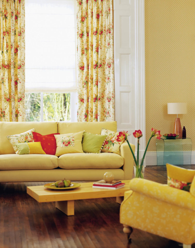 When added to the already sunny yellow living room, these strawberry motif curtains add a charming, quaint detail that picks up the color of the accent pillows and of the beautiful vase of flowers.
