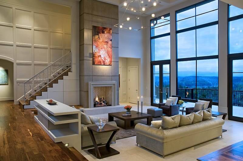 A great room with cathedral ceilings and floor-to-ceiling windows to the right that look out on the terrace. Matching end tables in sleek dark wood complement the squat dark wood coffee table in the center of the seating arrangement. A single glass-topped table sits between the two armchairs.