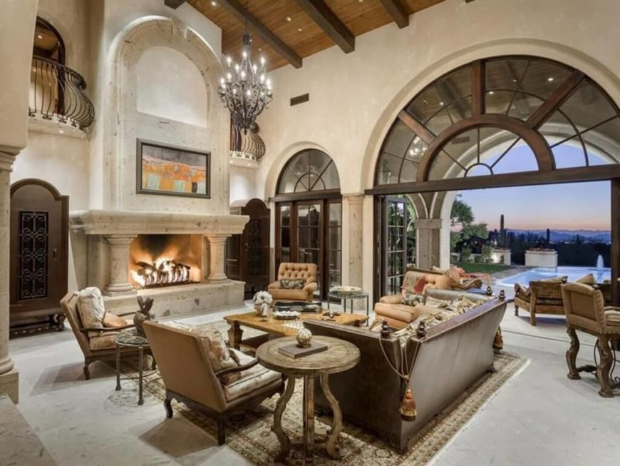 A stately traditional living room with soaring ceilings and huge windows and doors that lead outside to the pool and patio. The end tables in this room are distressed wood with carved details. Two of the smaller end tables have marble tops.